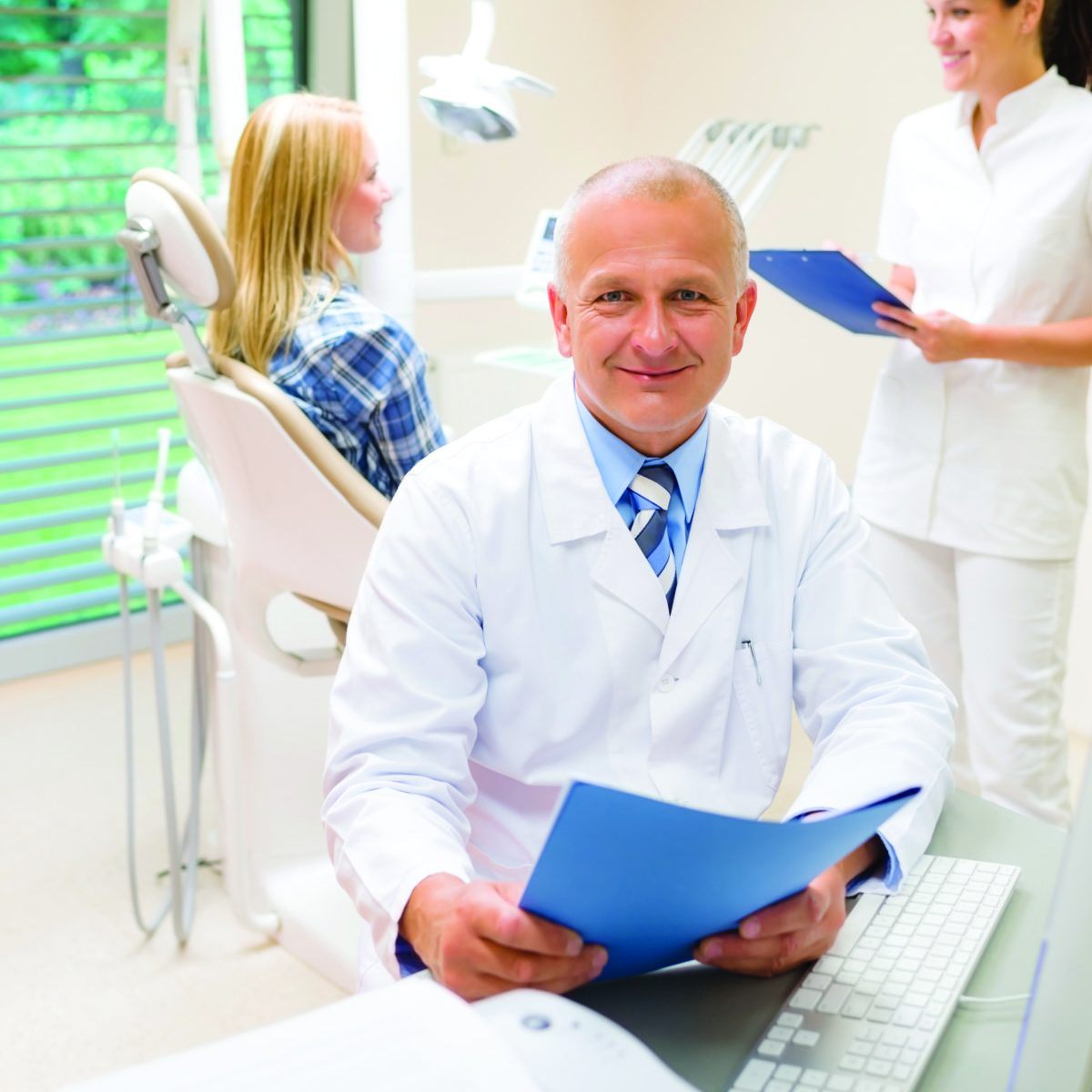 Mature dentist surgeon sitting at dental clinic nurse with patient
