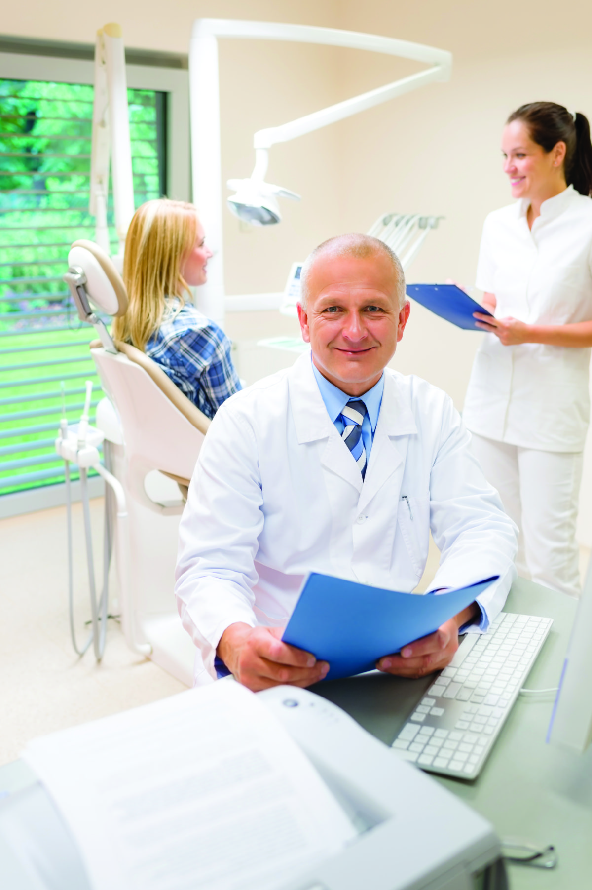 Mature dentist surgeon at dental clinic patient